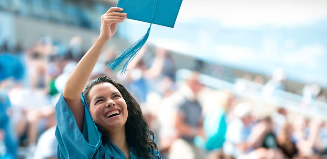 A graduate throwing a mortarboard into the air